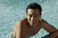 Young man in swimming pool smiling - Yukmin