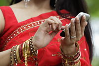 Close up of Indian woman texting on phone - Alex Mares-Manton