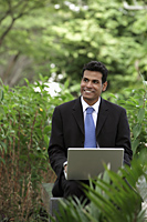 Indian man smiling while working on laptop with green plants in foreground and background - Alex Mares-Manton