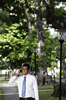 Indian man talking on phone under trees - Alex Mares-Manton