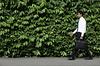 Indian man walking in front of green leafy hedge. - Alex Mares-Manton