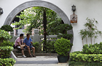 Two men sit inside circular door of park. Hong Kong - Alex Mares-Manton