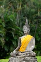 Stone Buddha in front of trees at Wat Yai Chaya Mongkol Temple, Thailand - Alex Mares-Manton