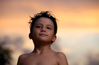 Young boy with goggles on his head at sunset. - Yukmin