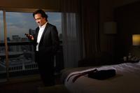 man wearing suit in hotel room looking at phone - Yukmin