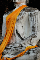 Cropped shot of stone Buddha wearing yellow robe, Thailand - Alex Mares-Manton