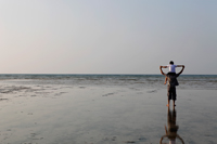 Boy sitting on father's shoulders and holding hands and looking at the ocean - Yukmin