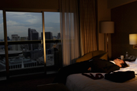 man wearing suit and laying down on bed in hotel room in the evening. - Yukmin