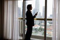 Man wearing suit holding phone looking out window - Yukmin