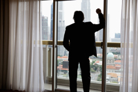 Rear view of business man looking out of window at buildings - Yukmin