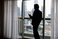 Profile of businessman near window with city as background - Yukmin