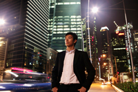 Young man standing on street at night with buildings in background - Yukmin