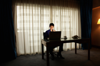 Young man sitting at a desk working on computer in the evening - Yukmin