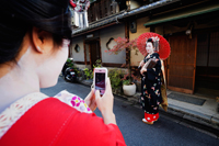Woman taking photo of Geisha dressed up in traditional Japanese clothes - Travelasia
