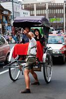 Couple taking a rickshaw ride on busy street in Tokyo Asakusa, Japan - Travelasia