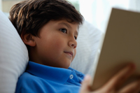 Head shot of young boy reading book - Yukmin