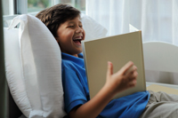 Young boy looking at book and laughing - Yukmin