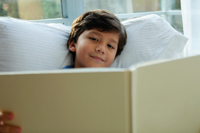Young boy reading book by window and smiling - Yukmin