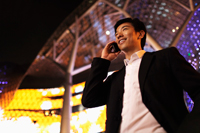 young man talking on phone smiling at night - Yukmin
