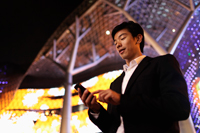 Young man in suit using phone in front of building at night - Yukmin
