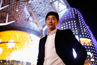 Young man in suit in front of lit building at night - Yukmin