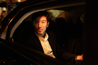 Young man sitting in car looking out of window at night - Yukmin