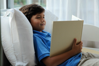 young boy sitting in bed reading book - Yukmin