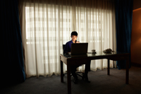 Young man sitting at desk working on laptop in the dark - Yukmin