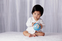 Chinese baby holding small globe - Yukmin