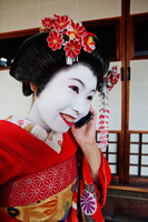Geisha talking on phone and smiling - Travelasia