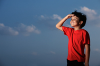Young boy wearing a red shirt looking out with hand shielding eyes - Yukmin