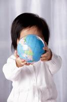 Baby holding small globe - Yukmin