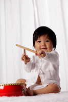 Chinese baby with red drum holding drum sticks - Yukmin