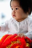 Chinese baby holding red toy - Yukmin