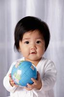 Head shot of Chinese baby holding small globe - Yukmin