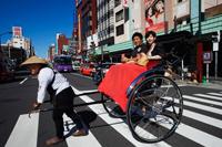 Couple in Rickshaw crossing the street.  Japan,Tokyo,Asakusa, - Travelasia