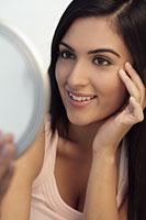 Young woman looking at mirror smiling while touching her face - Alex Mares-Manton