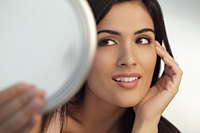 Head shot of young woman holding mirror and touching her face - Alex Mares-Manton