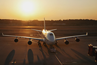 Airplane on tarmac, sun behind. Narita Airport, Japan - Travelasia
