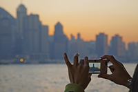 Woman Taking Photo of City Skyline and Victoria Peak. Hong Kong, China - Travelasia