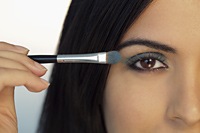 Cropped shot of young woman putting on eye make up. - Alex Mares-Manton