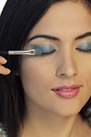 Head shot of young woman putting on blue eyeshadow - Alex Mares-Manton