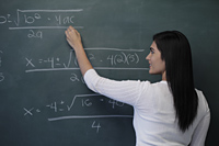 Rear view of young woman writing math equation on chalk board - Alex Mares-Manton