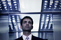 Young man in business suit standing in elevator - Alex Mares-Manton