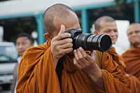 Monk taking photos with camera, Bangkok, Thailand - Travelasia
