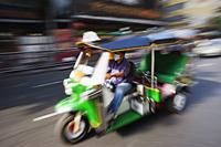 Tuk Tuk driving down the road. Bangkok, Thailand - Travelasia