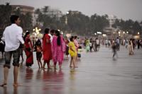 A crowd of people walking along the beach in Mumbai, India - Yukmin