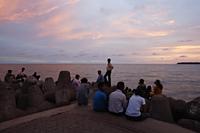 Small crowd gathered at the sea shore at sunset, Mumbai, India - Yukmin