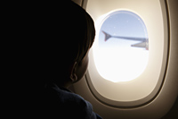 Young boy looking out of plane window - Yukmin