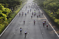 Cyclist riding down the road during a bike race - Yukmin
